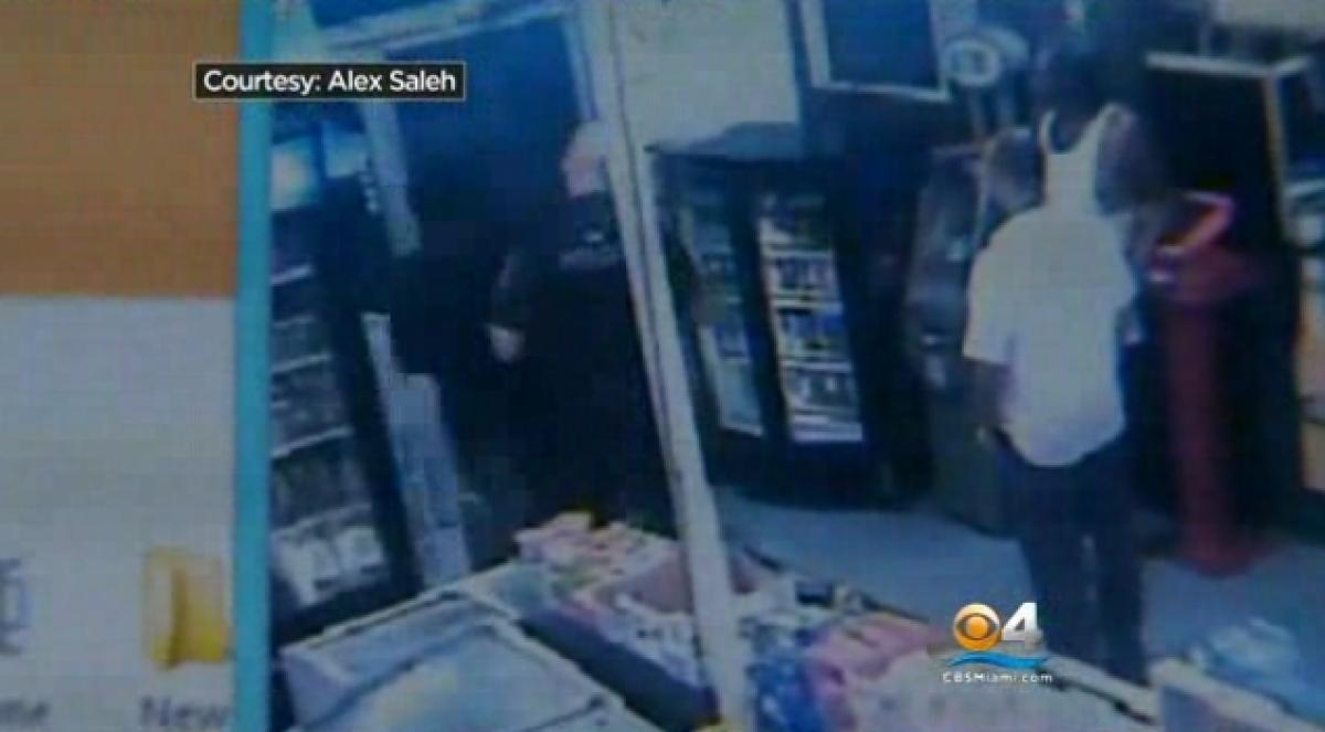 In one instance Sampson is seen restocking a cooler inside the store when a police accuses him of trespassing. The store owner claims the officer was told that Sampson works there but didn't care. (Courtesy Alex Saleh/CBS Miami)