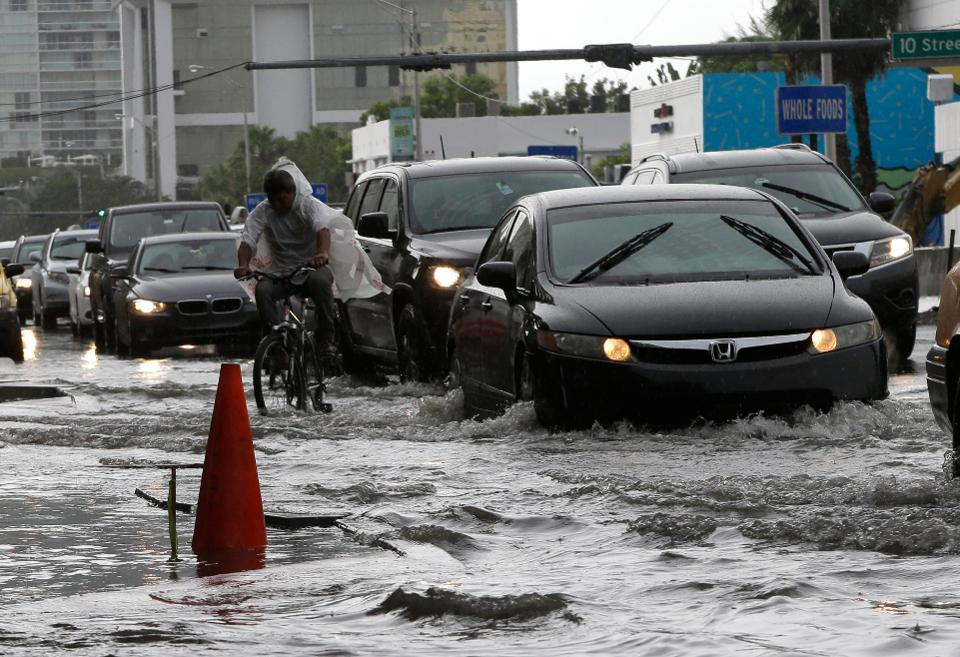 A cyclist and vehicles negotiate heavily flooded streets as rain falls, Tuesday, Sept. 23, 2014, in Miami Beach, Fla.