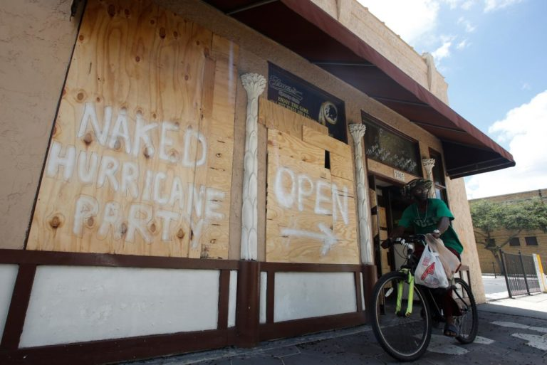 A man rides a bike past a bar with boarded up windows ahead for the arrival of Hurricane Irma in Tampa