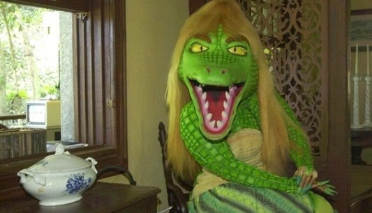 Alligator woman sitting in chair with tea
